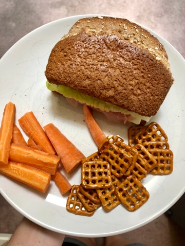 Deli meat sandwich with carrots and pretzels